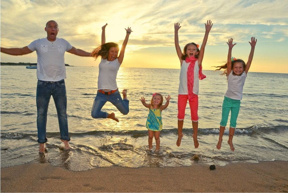 family, jumping on a beach